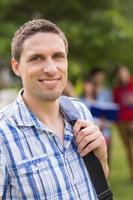gelukkige student die bij camera buiten op campus glimlacht foto