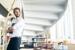 knappe intelligente kerel die een boek in een bibliotheek leest foto