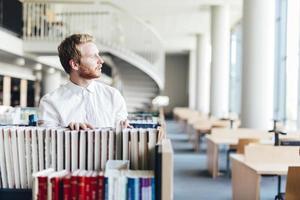 knappe student op zoek naar een boek in een bibliotheek