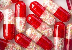 sluit omhoog van de rode capsules op witte achtergrond. foto