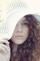 meisje achter kanten hoed foto