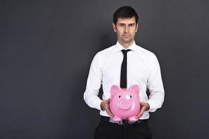 jonge man met spaarvarken (spaarpot), op donkere achtergrond foto