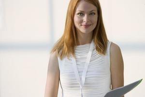 vrouw in witte mouwloze top met map, lachend, front vie foto
