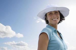 glimlachende vrouw die sunhat in openlucht draagt foto