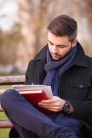 jonge man schrijven op een bankje foto