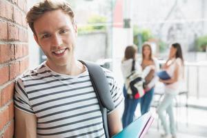 knappe student die en blocnotes glimlacht houdt