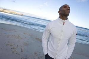 jonge man met de ogen gesloten op het strand, handen in de zakken foto