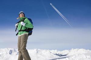 vliegtuig vliegt over vrouw backpacken op besneeuwde berg foto
