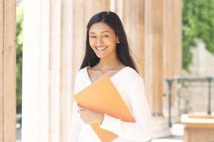 lachende jonge Aziatische student buitenshuis foto