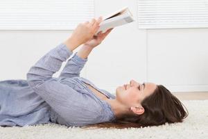 vrouw leesboek liggend op tapijt thuis