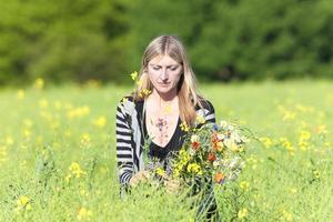 vrouw wilde bloemen plukken op de weide foto