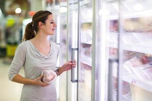jonge vrouw winkelen voor vlees in een supermarkt foto