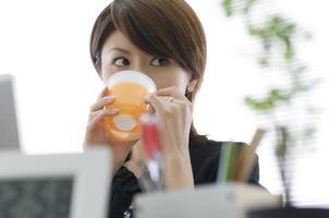 Japanse vrouw van in de twintig die drinkt foto