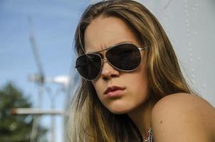 aantrekkelijk meisje in zonnebril over helikopter buiten foto