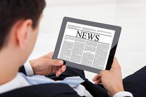 het nieuws van de zakenmanlezing op digitale tablet in bureau foto