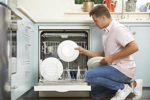 man laden vaatwasser in de keuken foto
