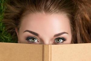 mooie jonge vrouw die over boekomslag kijkt foto