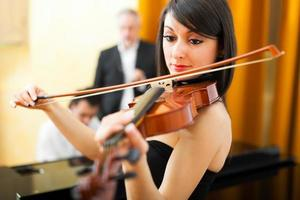 vrouw die viool speelt met een pianist foto