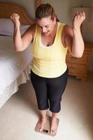 overgewicht vrouw met een gewicht van zichzelf op schalen in de slaapkamer