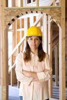 vrouw in veiligheidshelm met gekruiste armen in gedeeltelijk gebouwd huis foto