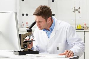 wetenschapper die door microscoop in laboratorium kijkt foto