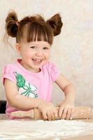 jong meisje kneden van deeg foto