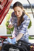 vrouw die het motoroliepeil van de motor van een auto onder kap met peilstok controleert foto