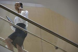 zakenvrouw met behulp van mobiele telefoon op trappen foto