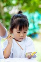 kind verf, schattig klein meisje is schilderen op haar hand foto