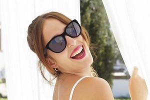 jonge vrouw lachend, met zonnebril, tussen witte gordijnen