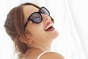 jonge vrouw die lacht, met zonnebril