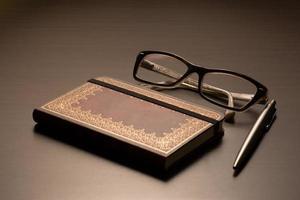 bril, notitieblok, pen.