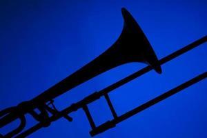 trombone silhouet geïsoleerd op blauw foto