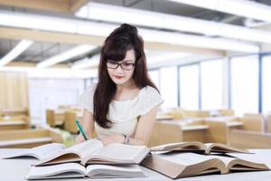 vrouwelijke leerling schrijven op het boek in de klas foto
