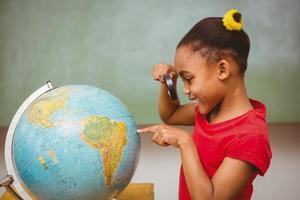 klein meisje kijken naar wereldbol door vergrootglas foto