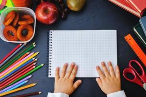 childrens handen met notebook op een schoolbord