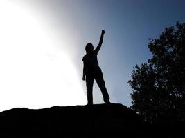 persoon met achtergrondverlichting door de arm op te tillen als een teken van overwinning foto