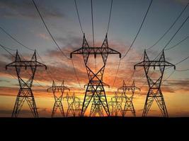 oneindige lijn van elektrische hoogspanningslijnen bij zonsondergang foto