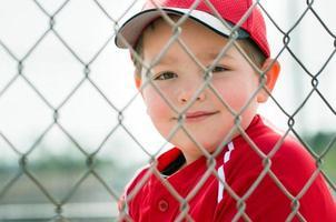 honkbalspeler die eenvormige zitting in dugout draagt foto