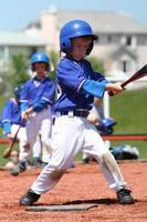 een jonge jongen die honkbal speelt en zijn tweede slag krijgt foto