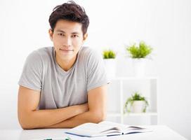 lachende ontspannen jonge man leesboek in de woonkamer foto