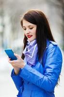 vrouw in blauwe mantel met smartphone foto
