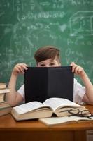kleine schattige jongen verstopt achter boek foto