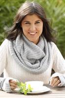 jonge vrouw met sjaal met een kopje thee foto