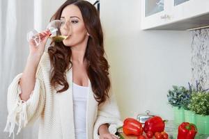 vrolijke jonge vrouw in schort op moderne keuken foto