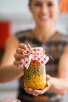 close-up op jonge huisvrouw die pot met groenten in het zuur toont