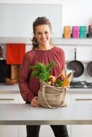 gelukkige jonge huisvrouw met lokale marktaankopen in keuken foto