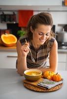 jonge huisvrouw die pompoensoep in keuken eet foto