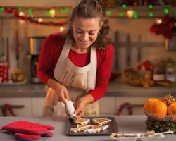 gelukkige jonge huisvrouw versieren kerstkoekjes in de keuken