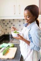 Afrikaanse huisvrouw die groene salade eet foto